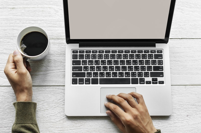 תמונה של מחשב נייד וכוס קפה לידה
